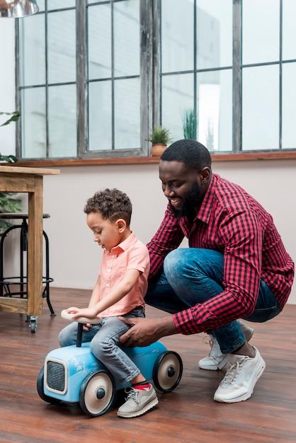 Zwarte vader die zoon met het drijven stuk speelgoed auto helpt Gratis Foto