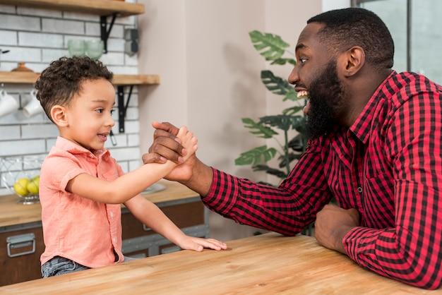 Zwarte vader en zoon arm worstelen Gratis Foto