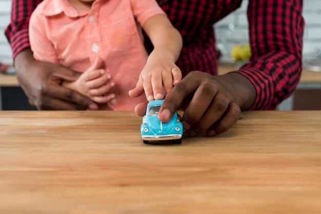 Zwarte vader en zoon spelen met speelgoedauto op tafel Gratis Foto