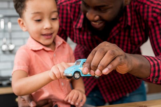 Zwarte vader en zoon spelen met speelgoedauto Gratis Foto