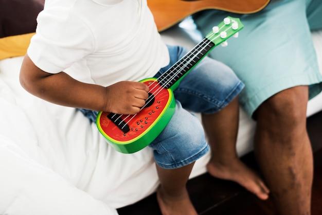 Zwarte vader geniet van gitaar spelen met zijn kind samen geluk Premium Foto