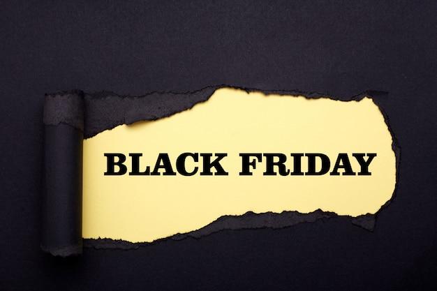 Zwarte vrijdag. gat in het zwarte papier. gescheurd. geel papier. samenvatting Premium Foto