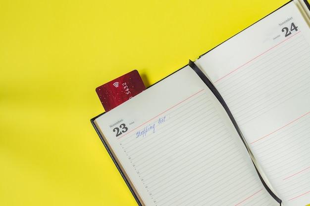 Zwarte vrijdag verkoop concept. boodschappenlijstje in notitieblok en bankkaart als bladwijzer Premium Foto