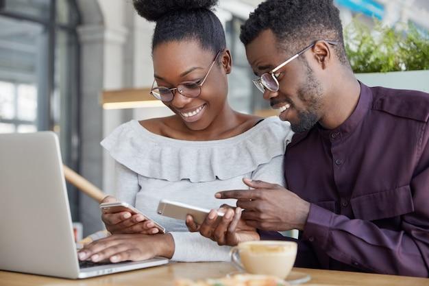 Zwarte vrouw en man hebben een informele ontmoeting, zijn blij om foto's op smartphone te bekijken, een bril te dragen, werken samen bij een gemeenschappelijk project via laptop Gratis Foto