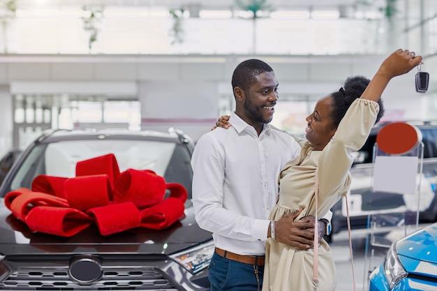 Zwarte vrouw is blij nadat ze van haar man een auto heeft gekregen Premium Foto