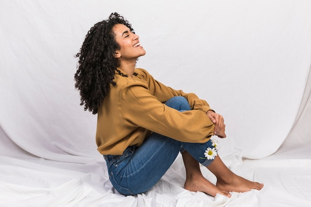 Zwarte vrouw zitten met madeliefjebloemen in jeans manchetten Gratis Foto
