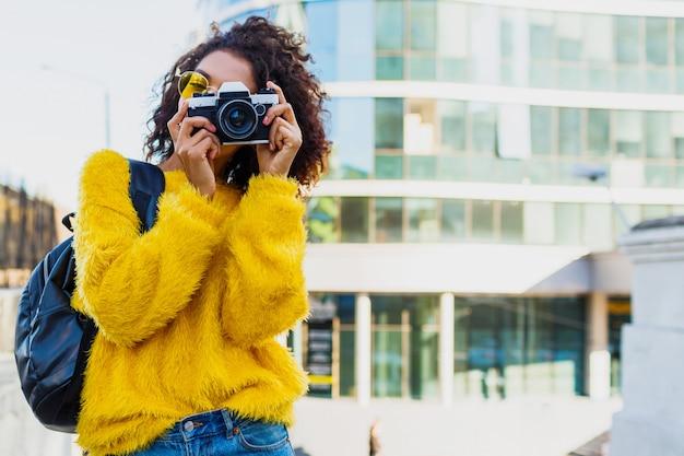 Zwarte vrouwelijke fotograaf die foto's maakt op moderne architectuur Gratis Foto
