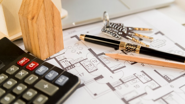 Zwarte vulpen; potlood; toetsen; houten huis blok en rekenmachine op blauwdruk Gratis Foto