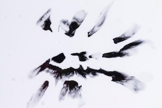 Zwarte waterverfvlekken die op vlotte witte oppervlakte worden geïsoleerd Gratis Foto