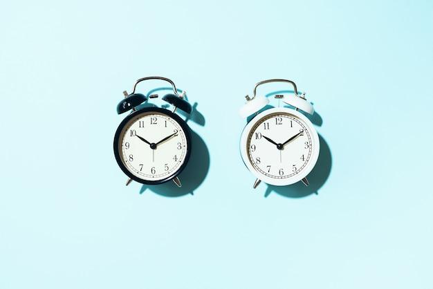 Zwarte wekker en witte met harde schaduw op blauwe achtergrond. Premium Foto