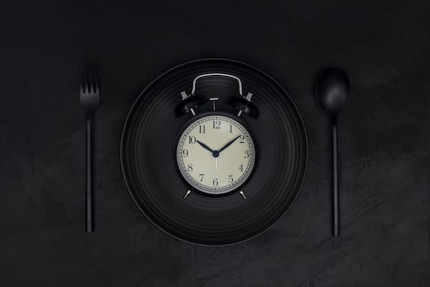 Zwarte wekker op zwarte plaat met lepel en vork op zwarte achtergrond. zwart zwart-wit concept. Premium Foto