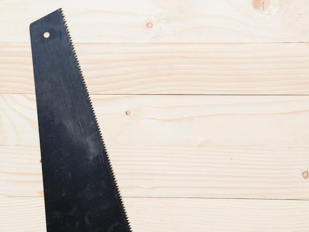 Zwarte zaag op houten tafel Gratis Foto