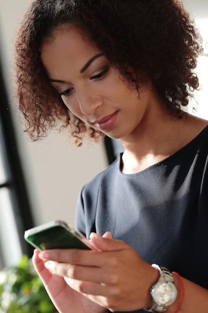 Zwarte zakenvrouw in strikte zwarte jurk haar e-mails controleren aan de telefoon Gratis Foto