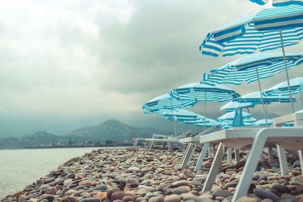 Zwarte zee en kiezelstrand met parasols en ligstoelen tegen bergen. zee vakantie en ontspannen tijd Premium Foto