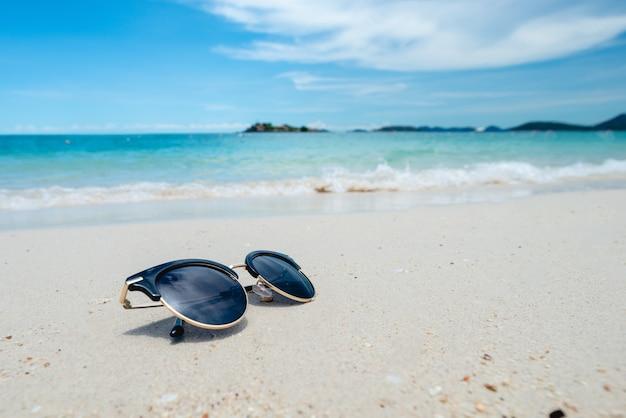 Zwarte zonnebril op de zee achtergrond. prachtig zandstrand als zomer-, reis- en vakantieconcept. concept vakantie. chillen op de zee. kopieer ruimte voor bericht. Premium Foto