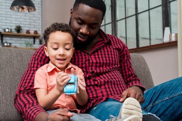 Zwarte zoon en vader zitten met kleine speelgoedauto Gratis Foto