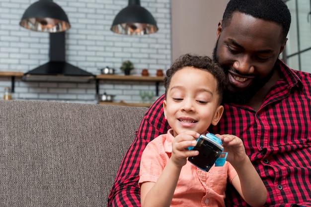 Zwarte zoon en vader zitten met speelgoedauto Gratis Foto