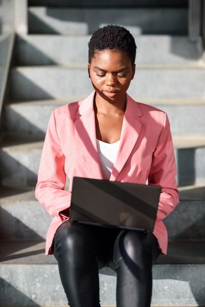 Zwartezitting op stedelijke stappen die met een laptop computer werken Premium Foto