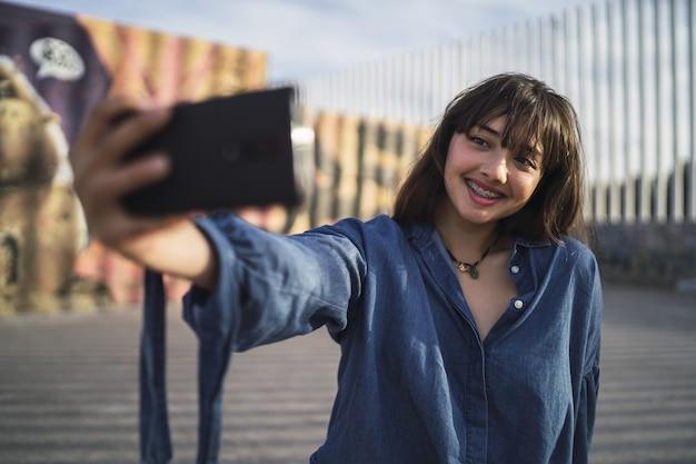 Zwartharig meisje dat een foto van zichzelf neemt achter een gebouw Gratis Foto