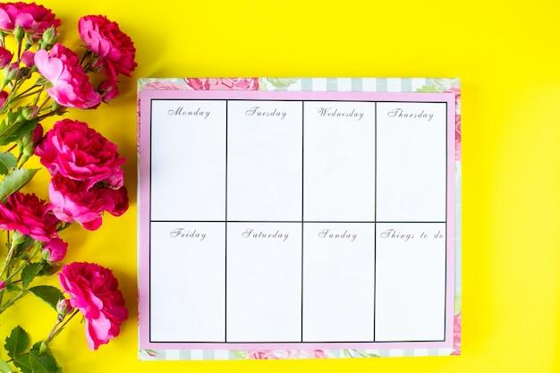 Zweefvliegtuig met notities en takenlijst op een gele achtergrond met roze briefpapier en bloemen. bedrijfsconcept. bovenaanzicht Gratis Foto