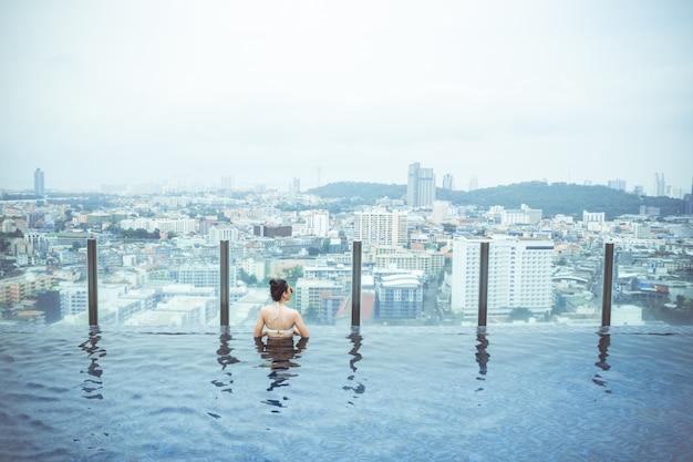 Zwembad op dakbovenkant met mooie stadsmening, de mening van de zeegezichtstad, pattaya, thailand Premium Foto