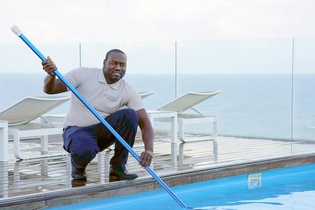 Zwembadreiniger tijdens zijn werk. Premium Foto