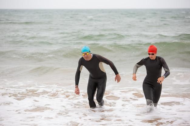 Zwemmers in wetsuits in zeegolven Gratis Foto