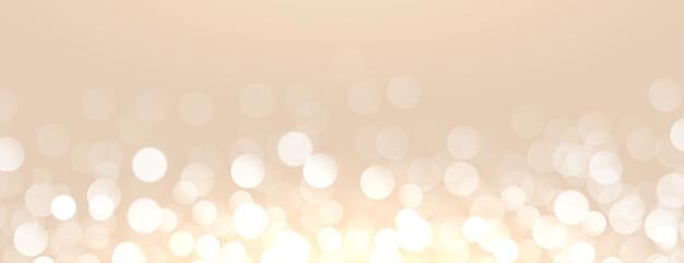 Aantrekkelijke gouden achtergrond met bokeh lichteffect Gratis Vector