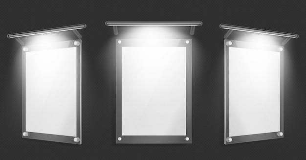 Acryl poster, leeg glazen frame met verlichting hangen aan de muur geïsoleerd op zwarte achtergrond Gratis Vector