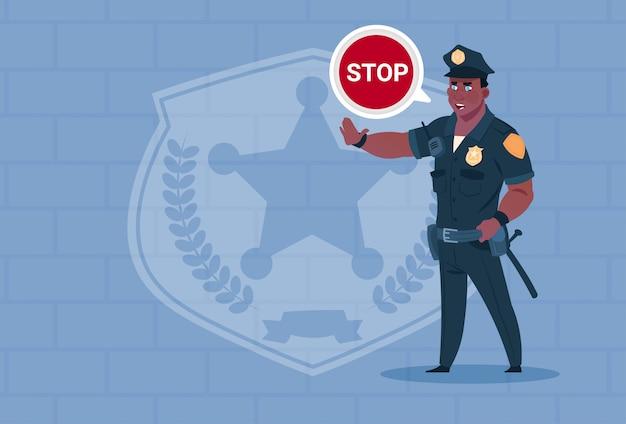 Afrikaanse amerikaanse politieagent met stop chat bubble dragen uniform cop guard over baksteen achtergrond Premium Vector