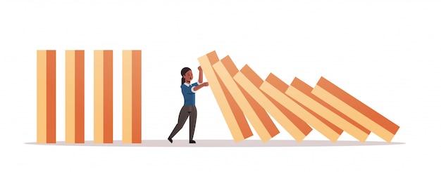 Afro-amerikaanse zakenvrouw stoppen domino-effect crisismanagement kettingreactie financieren interventie conflictpreventie concept horizontale volledige lengte Premium Vector