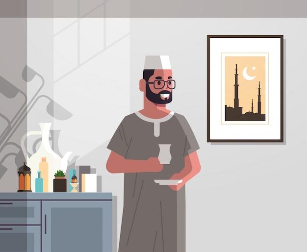 Arabische man in traditionele kleding drinken koffie vieren ramadan kareem heilige maand moderne woonkamer interieur plat verticaal portret Premium Vector