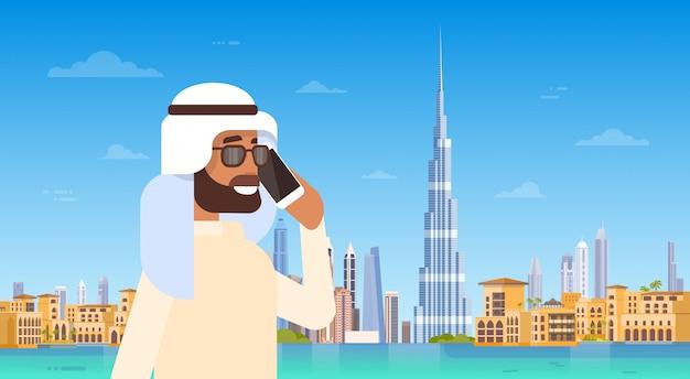 Arabische man spreken op mobiele slimme telefoongesprek over dubai skyline panorama, moderne gebouw stadsbeeld Premium Vector