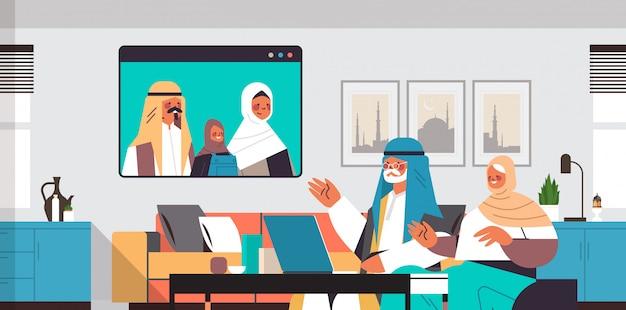 Arabische ouders en dochter met virtuele ontmoeting met grootouders tijdens video-oproep familiechat communicatieconcept woonkamer interieur portret horizontale afbeelding Premium Vector