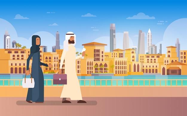Arabische paar walking dubai, moderne gebouw cityscape skyline panorama zakelijke reizen en toerisme co Premium Vector