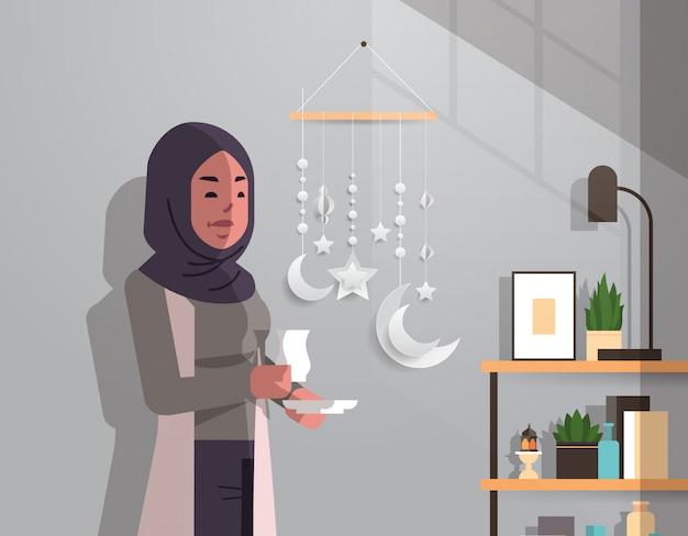 Arabische vrouw in traditionele kleding drinken koffie vieren ramadan kareem heilige maand moderne woonkamer interieur plat verticaal portret Premium Vector