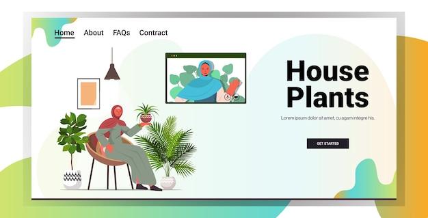 Arabische vrouwen die voor kamerplanten zorgen meisjes met virtuele bijeenkomst tijdens videogesprek woonkamer interieur horizontale kopie ruimte Premium Vector