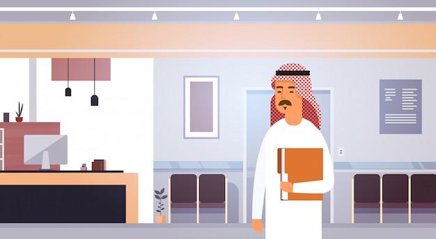 Arabische zaken man holding folder met documenten ondernemer in modern kantoor Premium Vector