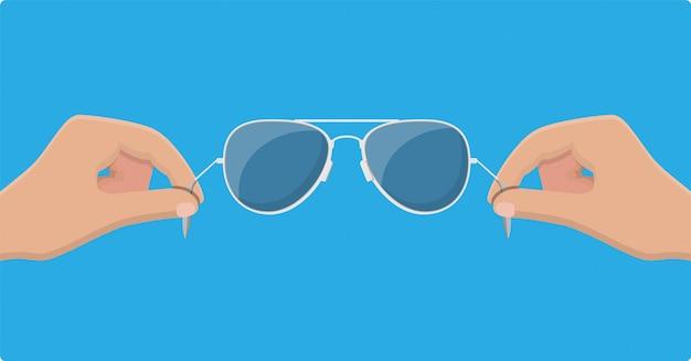 Aviator zonnebril in de hand. beschermende bril. Premium Vector