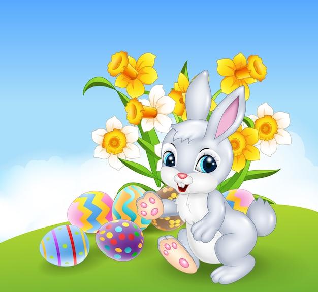 Beeldverhaal gelukkig konijntje met kleurrijke paaseieren Premium Vector
