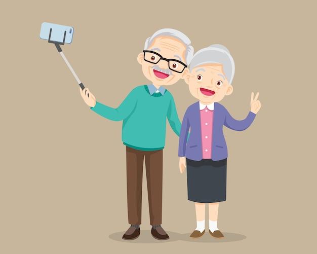 Bejaard paar die selfie foto met smartphone maken Premium Vector