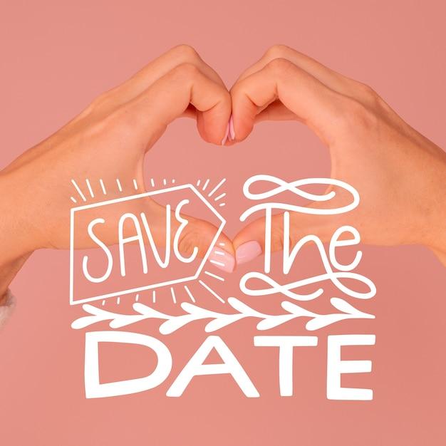 Bewaar de datum belettering met handen maken van hartvorm Gratis Vector