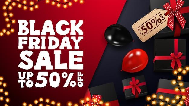 Black friday-uitverkoop, tot 50% korting, rode en blauwe kortingsbanner met zwarte cadeautjes, slingerframe en rode en zwarte ballonnen, bovenaanzicht. Premium Vector