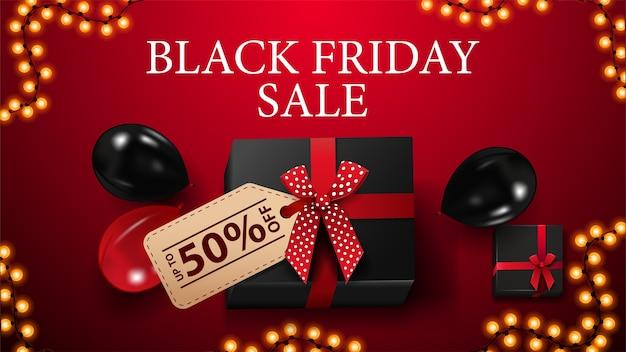 Black friday-uitverkoop, tot 50% korting, rode kortingsbanner met zwart cadeau met prijskaartje met aanbieding, slingerframe en rode en zwarte ballonnen, bovenaanzicht Premium Vector