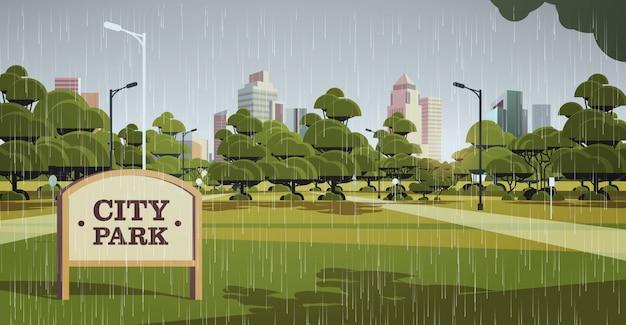 Bord in stadspark regen druppels vallende regenachtige zomerdag skyline skyskraper gebouwen stadsgezicht Premium Vector