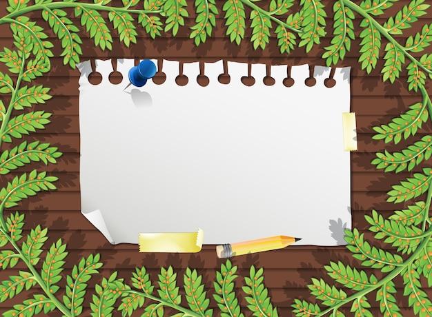 Bovenaanzicht van blanco papier op tafel met bladeren elementen Gratis Vector