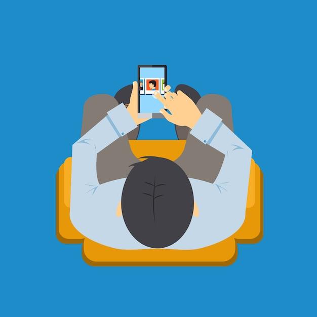 Bovenaanzicht van een man zittend in een stoel met behulp van een app op zijn mobiele telefoon met het scherm zichtbaar terwijl hij navigeert met zijn vinger vectorillustratie Gratis Vector