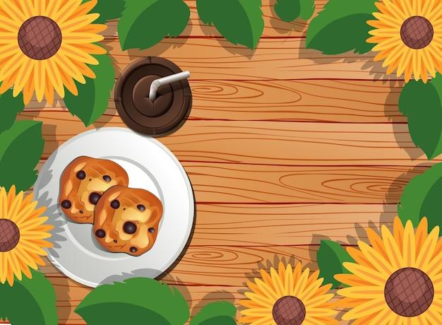 Bovenaanzicht van houten tafel met dessert en ijskoffie en bladeren en zonnebloem element Gratis Vector