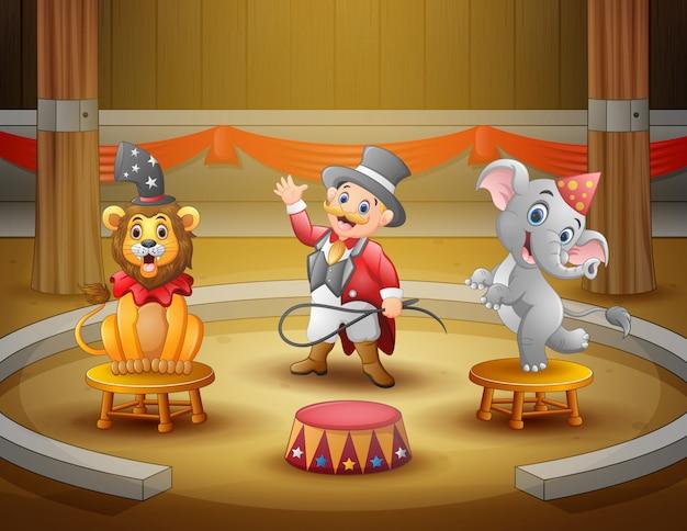 Cartoon circusdirecteur met dieren in de arena Premium Vector