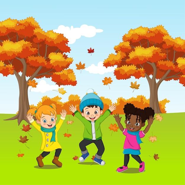 Cartoon gelukkige kinderen spelen in herfst achtergrond Premium Vector